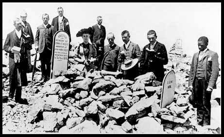 Men posing at the supposed grave of a girl eaten by Pike's Peak mountain rats