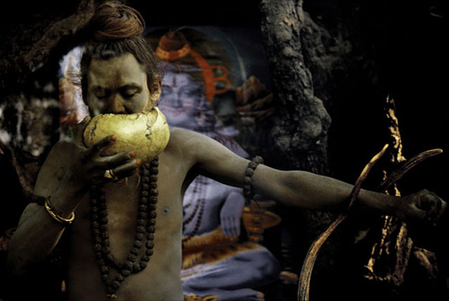 An Aghori man drinks ritual alcohol from a human skull