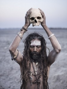 An Aghori man with a human skull