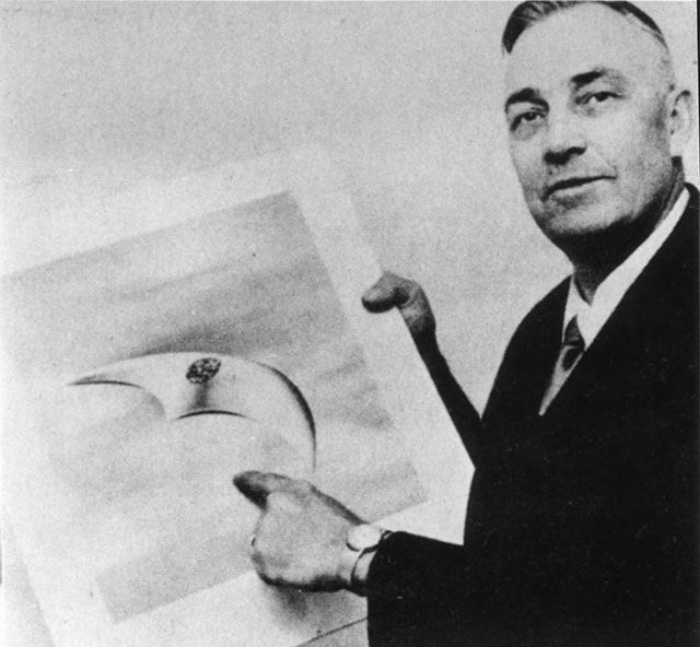Kenneth Arnold holds a sketch of a crescent-shaped flying saucer