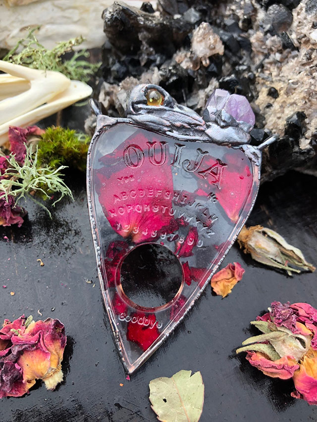 Ouija board planchette with rose petals