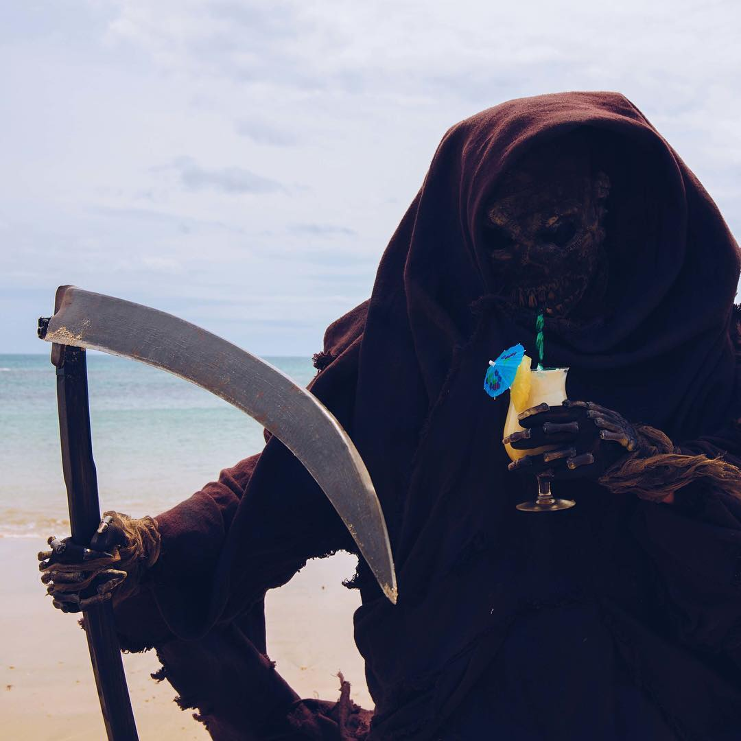 Death enjoys a pina colada on the beach