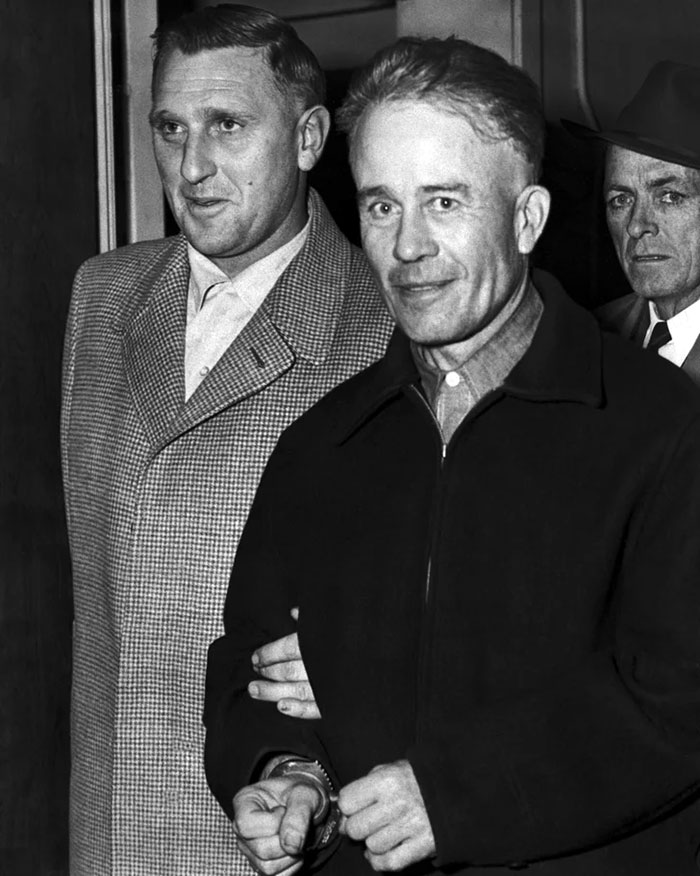 Ed Gein in handcuffs, smiling for the camera