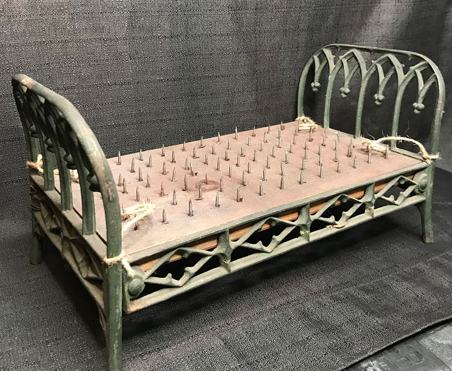 Miniature spiked torture bed